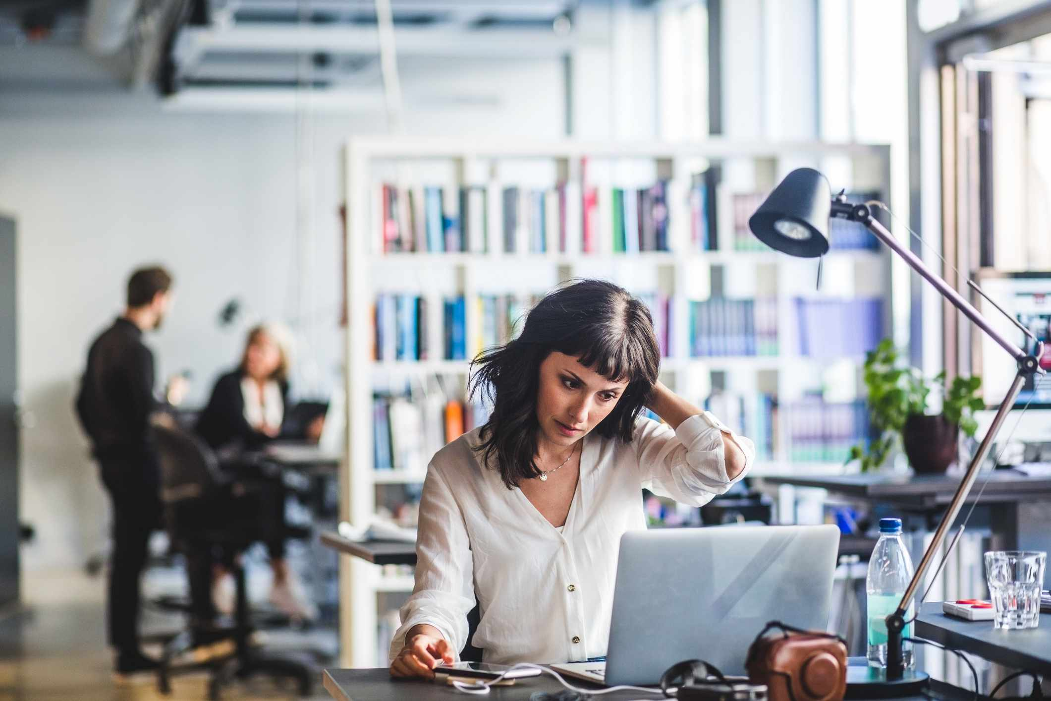A woman working at her desk in a busy office.