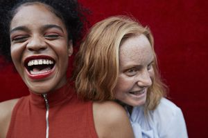Two people smiling and laughing while standing against a red wall