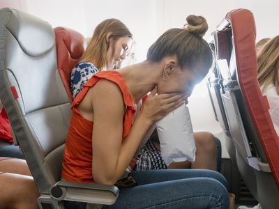 woman breathing into paper bag on airplane
