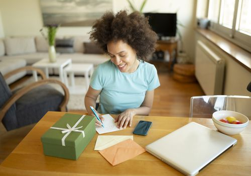 Happy African-American young woman happy about writing a letter, a practice that has powerful benefits