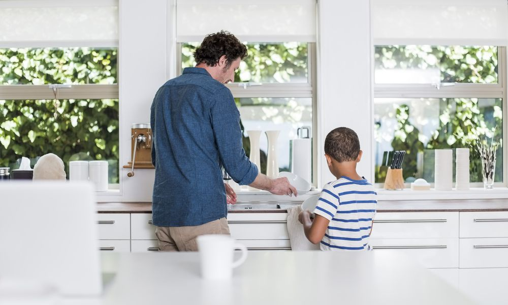 Rear view of father and son cleaning dishes in kitchen at home