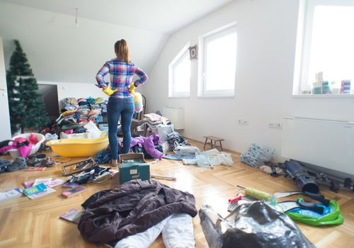 Lady standing in the center of the room full of clutter