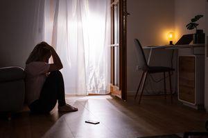 woman sitting in her bedroom looking distressed