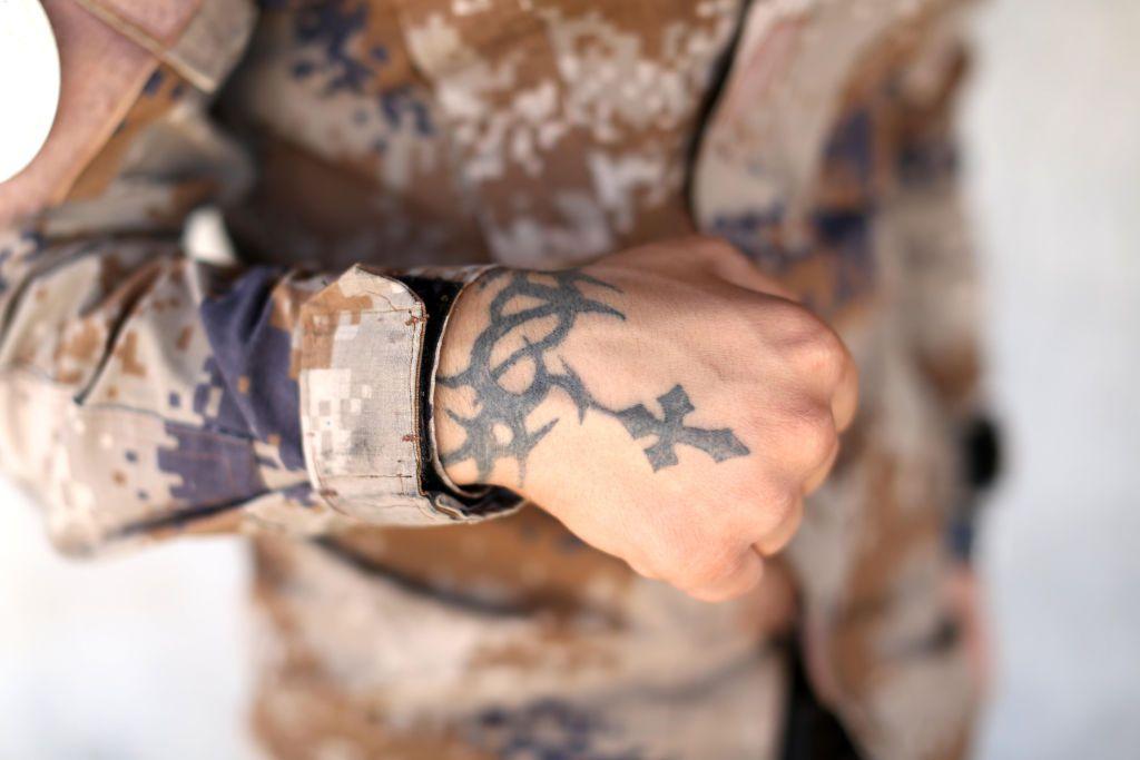 Hand with cross tattoo.