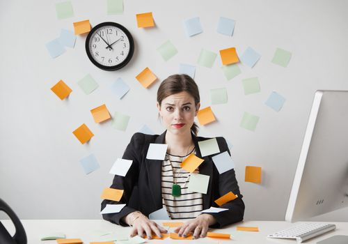 a woman in an office with post-its stuck on her and the wall behind her