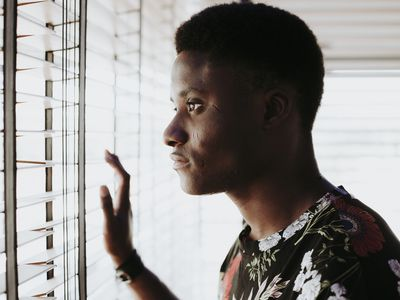 Pensive young man looking out of window