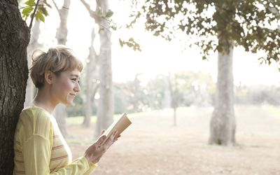 Japanese woman reading book in park