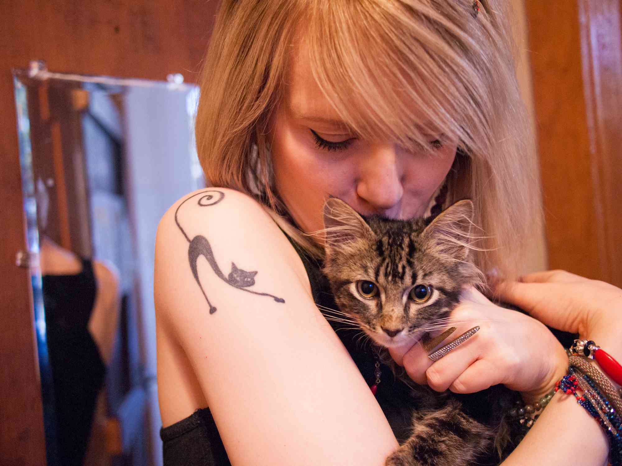 Woman holding cat with cat tattoo