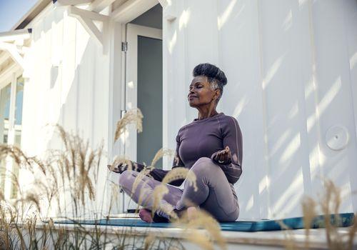 BIPOC woman meditating outside.