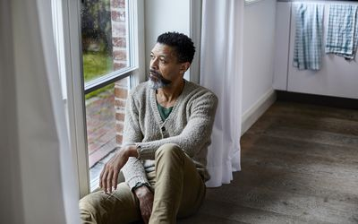 Depressed BIPOC man looking out window