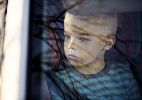 Depressed boy looking out the window of the car