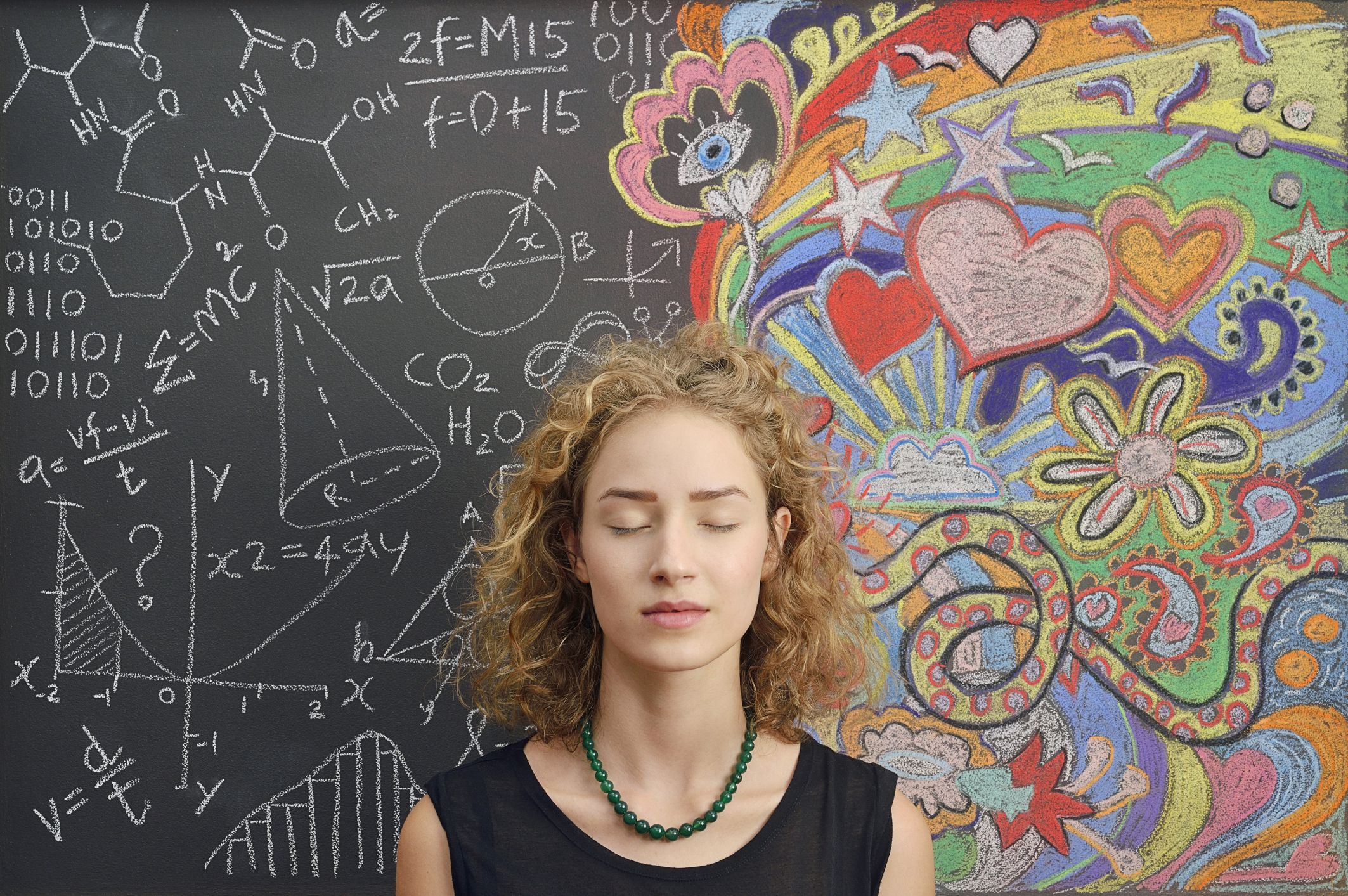 woman with closed eyes standing in front of a chalkboard