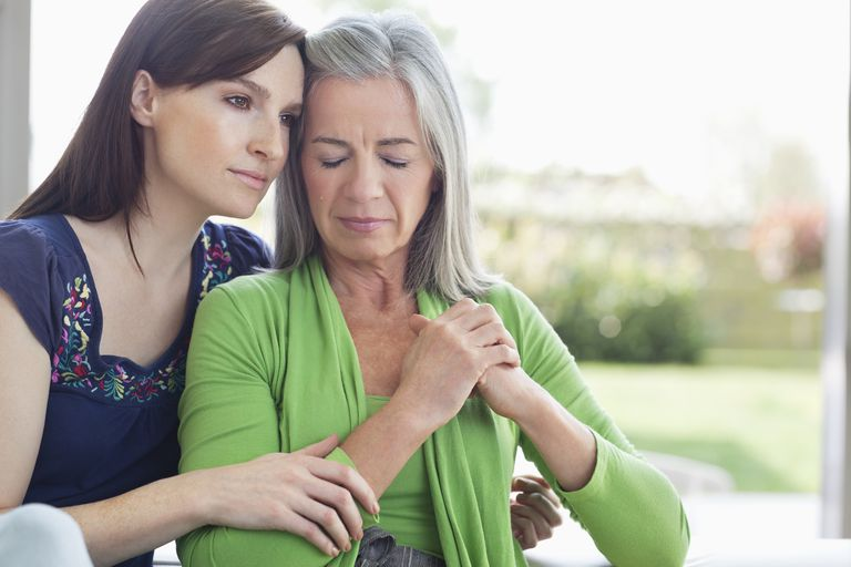 young woman embracing sad-looking older woman