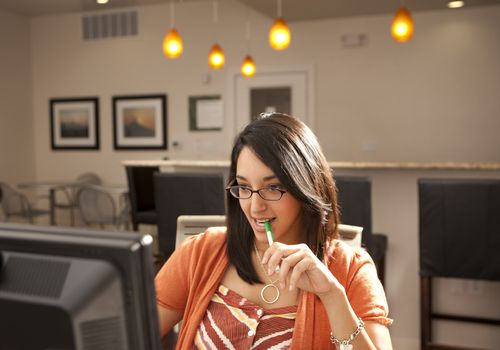 Woman chewing on pen and looking at computer