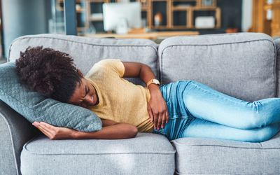 Black woman lying on the couch with period cramps