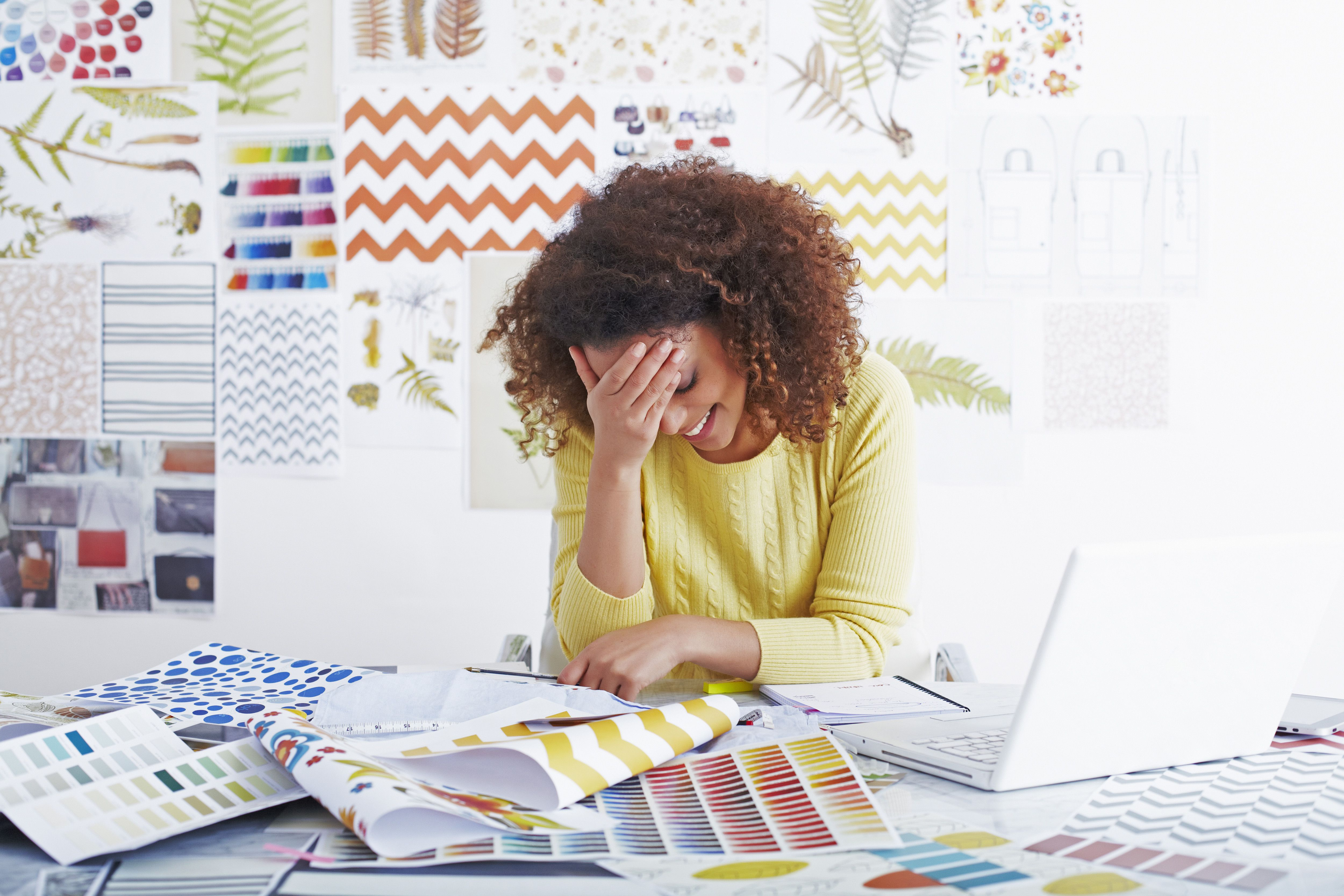 Woman smiling at her desk looking at pattern and color samples.