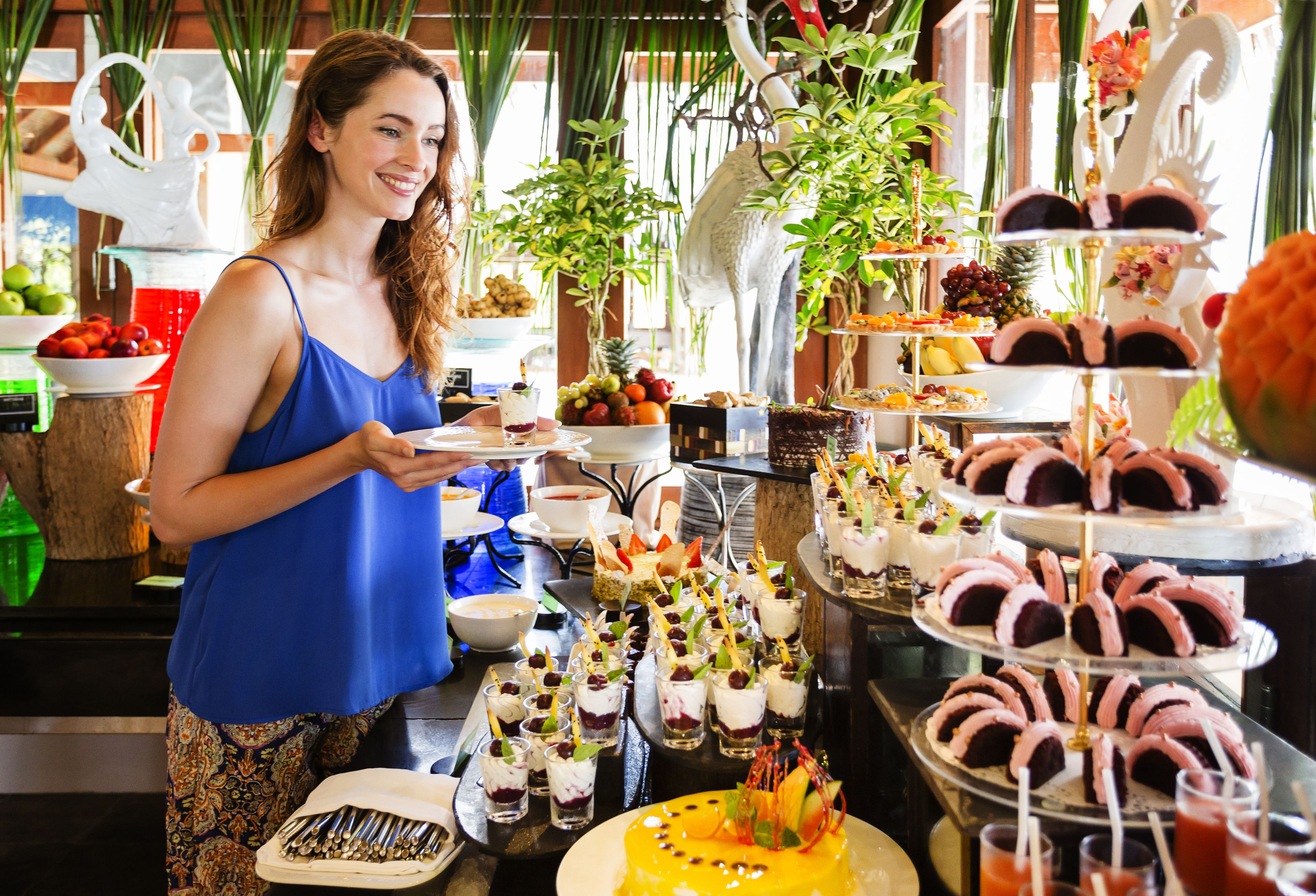 Young woman at dessert table of resort buffet