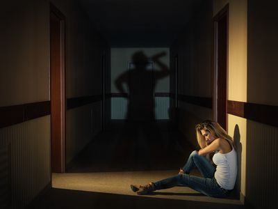 a woman sitting in a hallway and a man's shadow drinking