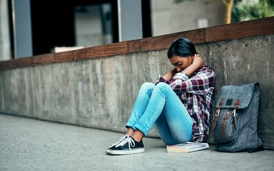 A person sits on the floor against a wall with a backpack next to them.
