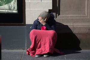 Person experiencing homelessness sitting on a sidewalk with a red blanket over their legs. They are holding a cup and covering their face with their hand.
