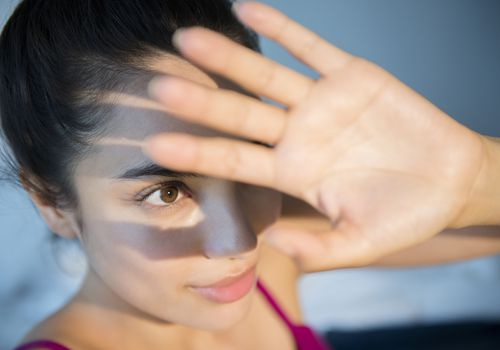 Woman holding up her hand to protect face from sunlight