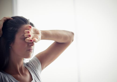 Woman not feeling well with her hand on her head