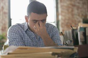 Stressed man with headache at desk