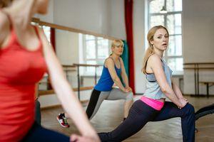 Three women doing a hip flexor stretch in a fitness class