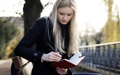Woman writing in journal on park bench