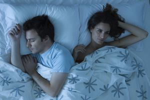 a couple in bed, the man is asleep, the woman is awake