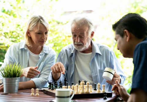Woman and man playing chess with an older man