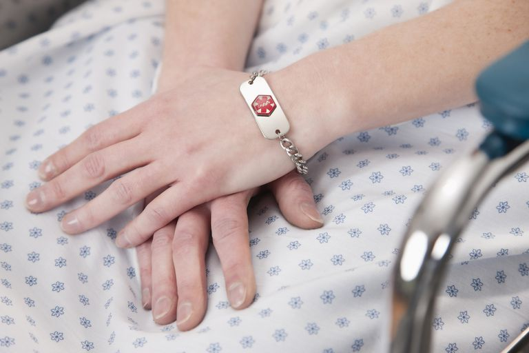 Close-up of female patient hands with medical identity bracelet