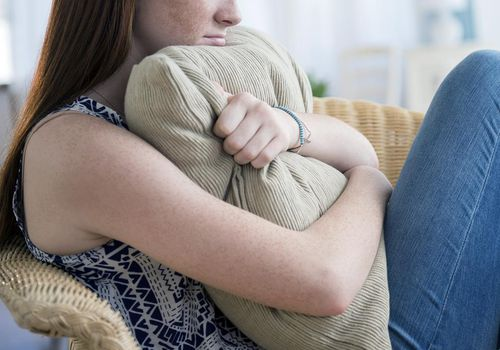 Teenage girl hugging a pillow and sitting in a chair