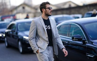 White man wearing grey suit, and black t-shirt within. He has sunglasses on and is walking next to dark cars