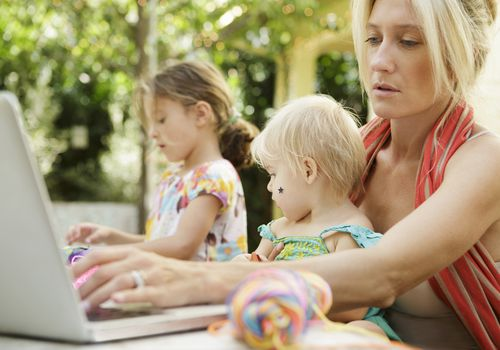 Mother multi tasking with children and laptop