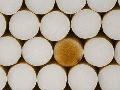 Stack of cigarettes, one with a stained filter