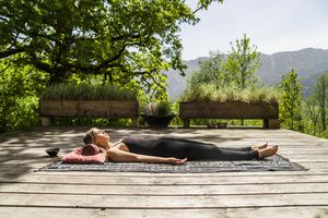 Woman in Savasana on a yoga blanket.