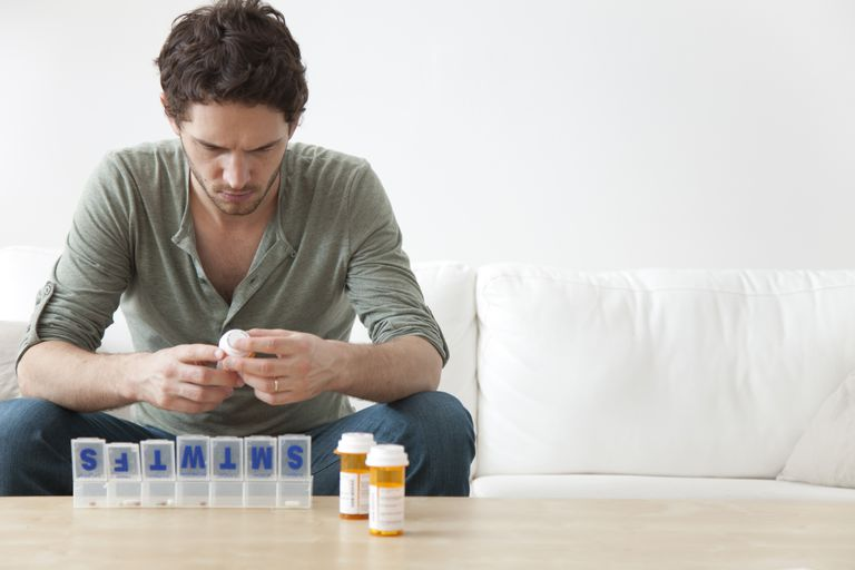 Man putting medication into pill organizer