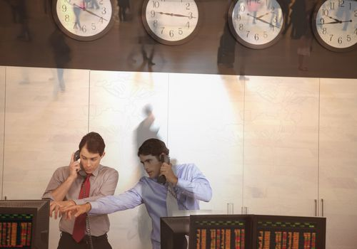Two male stock brokers talking on phones and pointing at computer screens