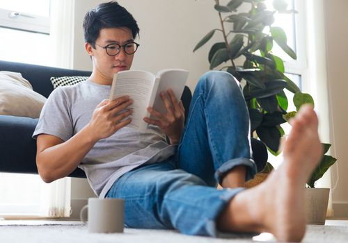 Man sitting down reading a book.
