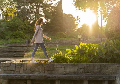 Woman walking on wall in park