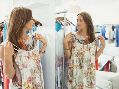 woman holding up dress in mirror in store