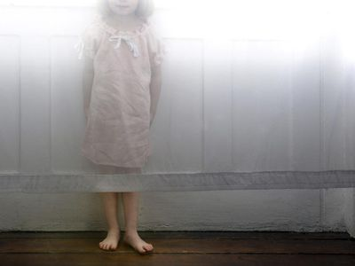 girl standing behind curtain