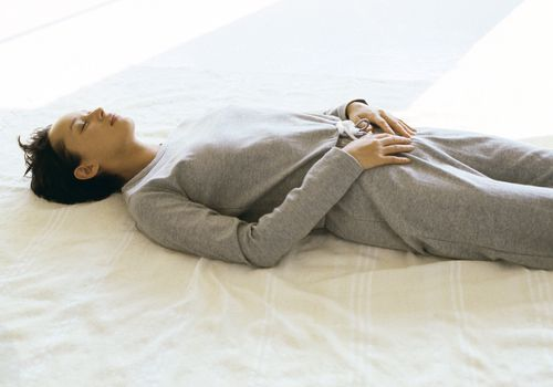 Woman wearing athletic wear lying on back with hands placed on lower abdomen