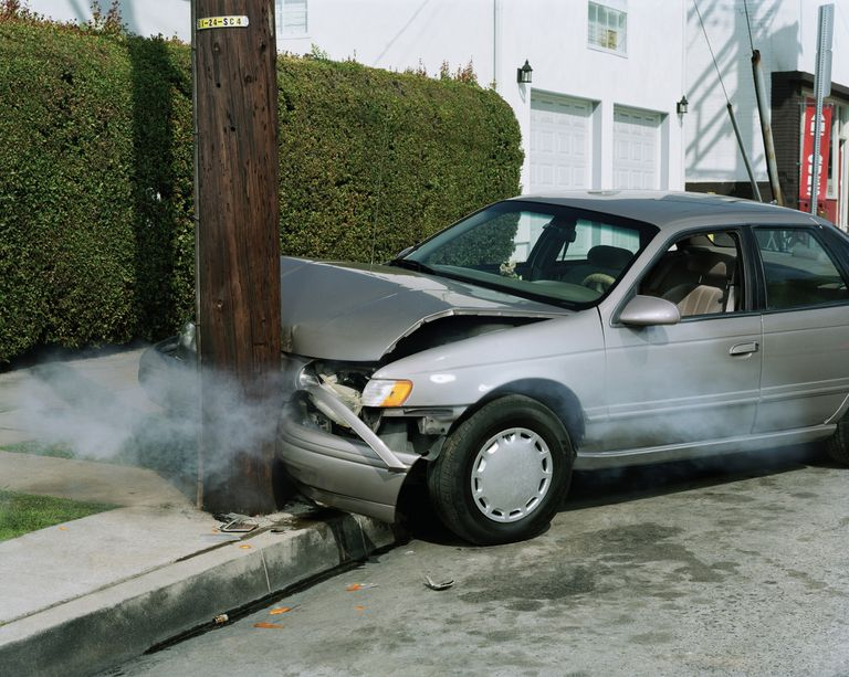 Car crash against telephone pole by road