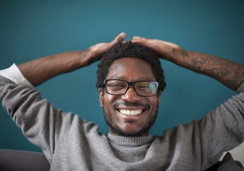 A happy man wearing glasses is resting his hands over his head