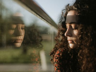 A woman with a sad expression looking out the window.