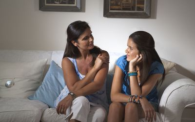 A mom talks with her teenage daughter on a sofa.