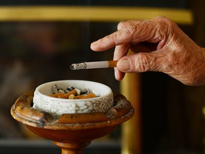 Close up of a wrinkled, aged hand tapping ash into an ashtray