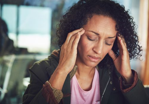 BIPOC person with a migraine holding her head